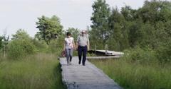 Couple walking bat bridge National Park Stock Footage