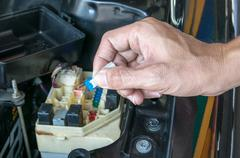 Auto mechanic checking a car fuse - stock photo