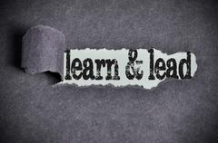 learn and lead word under torn black sugar paper - stock photo