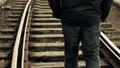 Man walking away in the middle of the rail tracks Stock Footage