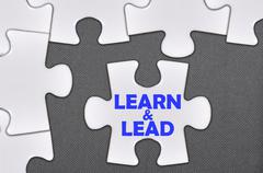 jigsaw puzzle written word learn and lead - stock photo