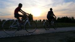 Stock Video Footage of Father on bicycle passing with daughters - bike, roller skate, scooter. Sunset.