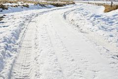 frozen winter asphalt road with snow - stock photo