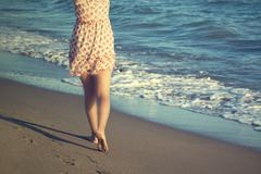 The legs of a woman walking on a beach Stock Photos