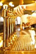 gold beer in the hand and beer taps - stock photo