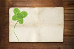 Clover symbol on old wood background with empty paper Stock Photos