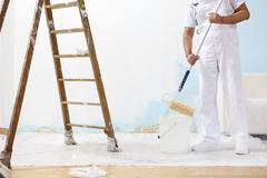painter man at work takes the color with paint roller from the bucket - stock photo