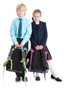 First grade pupils in school uniform with schoolbags in hands looking at camera - stock photo