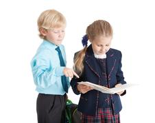 Stock Photo of First grade Caucasian couple of student talking together, isolated on white