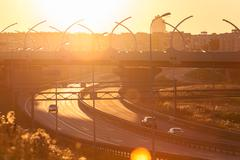 Bright sunset sun over highway junction, cars driving on the road - stock photo