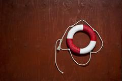 Red and white life buoy hanging on the side of a wood - stock photo
