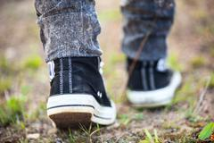Unrecognizable person in rubber shoes walking on footpath, rear view Stock Photos