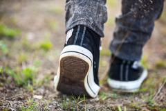 Unrecognizable person in running shoes walking on footpath, rear view Stock Photos