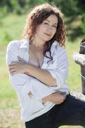 Stock Photo of Beautiful woman covering her breast with hands, looking at camera, summer sun
