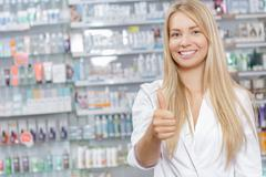 Young beautiful pharmacist standing in a drugstore - stock photo