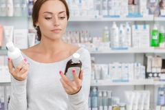 Beautiful girl can't decide what to buy in drugstore - stock photo
