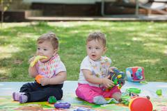 Babys, less than a year old, playing with  toys - stock photo