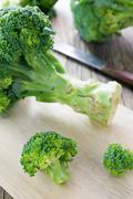 Fresh broccoli on a cutting board and knife Stock Photos