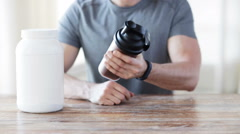 Close up of man with protein shake bottle and jar Stock Footage