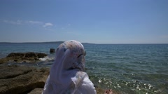 Muslim woman sitting on sea beach in Hvar 4K Stock Footage