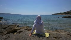 Muslim woman enjoying her view on the coast on Hvar island Stock Footage