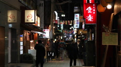 Foot and bicycle traffic in a small Nakano, Tokyo alley at night Stock Footage