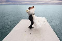 The groom is whirling his bride by the sea line. - stock photo