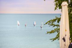Windsurfers on the horizon. - stock photo