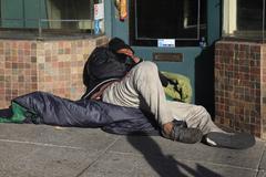 Homeless man sleeps on the street - stock photo