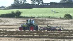 Tractor tows hayrake across field. Stock Footage