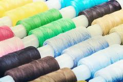 Multicolor bobbin threads on background Stock Photos