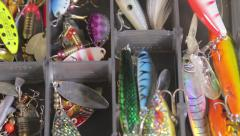 Various fishing lures and accessories in the box background Stock Footage