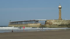 Tourists enjoy the summer weather on Whitby beach Stock Footage