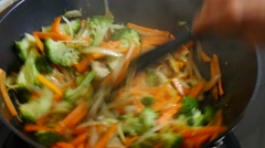 Cook carrots, onions and broccoli in wok Stock Footage