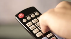 TV remote pointed at screen with fingers on buttons Stock Footage