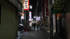 Pedestrians walking down a bright alley at night in Nakano, Tokyo Stock Footage