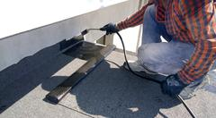 Roofer preparing part of bitumen roofing felt roll for melting by gas heater  Stock Photos