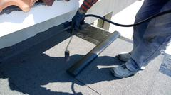 Stock Photo of Roofer preparing part of bitumen roofing felt roll for melting by gas heater