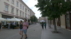 Women with green shirts walking on Nicolae Balcescu Street in Sibiu Stock Footage