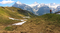 Aerial drone Swiss Alps female hiking snow ice healthy outdoor lifestyle terrain Stock Footage