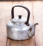 dirty classic aluminum kettle on wooden background - stock photo