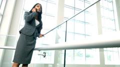 Female Asian Indian business advisor using smart phone on city atrium - stock footage