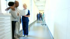 Caucasian female nurse consulting with African American patients in hospital Stock Footage