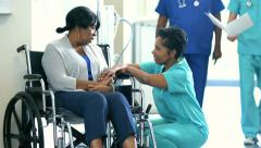 African American female nurse with patient in wheelchair consulting in hospital - stock footage