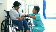Medical consultation with African American female staff and disabled patient - stock footage