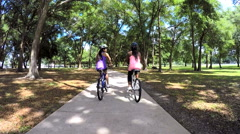 Young active multi ethnic girls riding bikes in park - stock footage