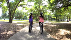 Young active multi ethnic females riding bikes in park Stock Footage