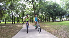Young slim multi ethnic girls riding bicycles in park Stock Footage