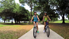 Young slim multi ethnic females riding bicycles in park - stock footage