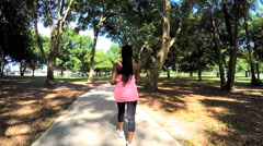 Young active African American fitness female enjoying power walking in park - stock footage